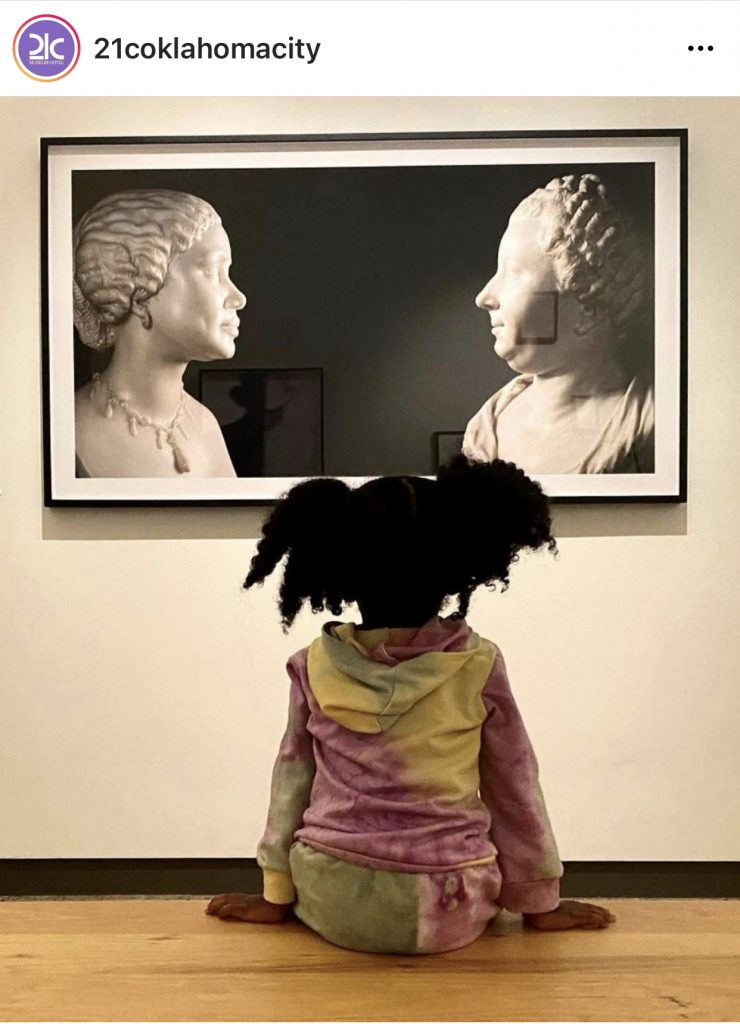 girl in front of a photo of two busts of women
